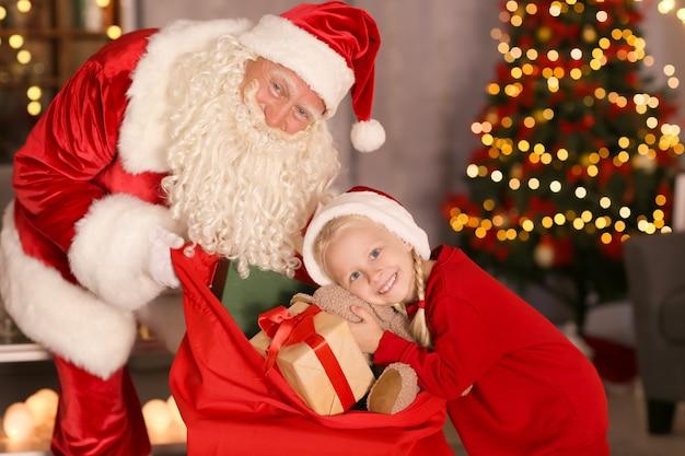 Mała dziewczynka wybiera prezent z torby prezentowej świętego mikołaja w udekorowanym pokoju