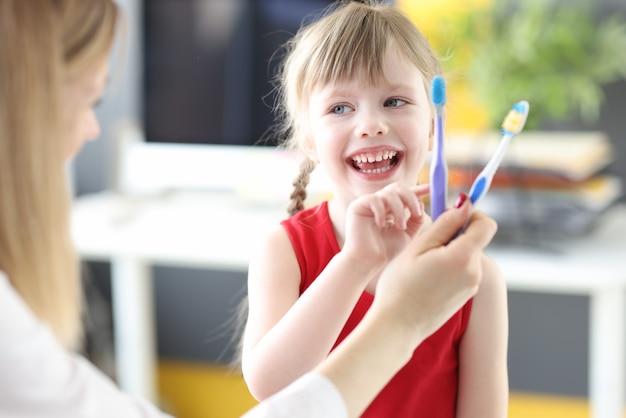 Mała dziewczynka wybiera szczoteczkę do zębów w gabinecie dentystów