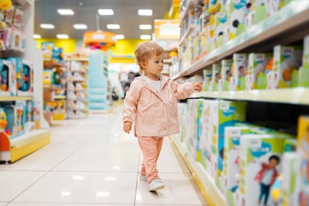 Mała dziewczynka wybiera zabawki w sklepie dla dzieci