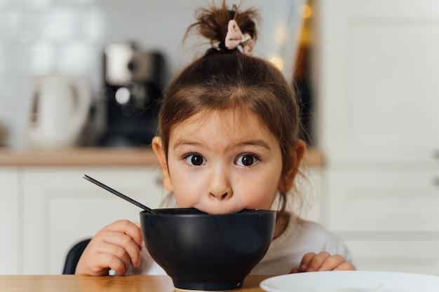 Mała dziewczynka wybredna zjadacz w domowej kuchni. nauka jedzenia łyżką. złe maniery dziecka przy stole