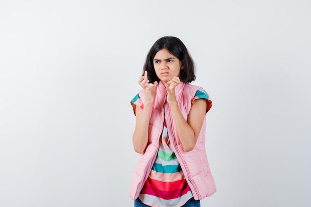 Mała dziewczynka wyciąga ręce trzymając coś, odwracając wzrok w t-shirt, kamizelkę puchową, dżinsy i wygląda na niezadowoloną. przedni widok.