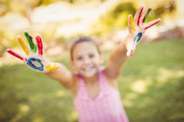 Mała dziewczynka wyciągając jej pomalowane ręce