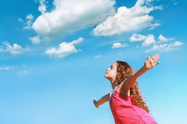 Mała dziewczynka wyciągnęła ręce i zamknęła oczy, ciesząc się świeżym powietrzem.