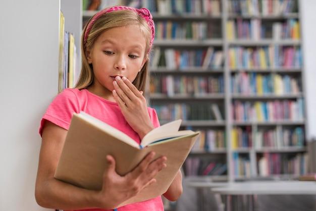 Mała dziewczynka wygląda na zszokowaną po przeczytaniu czegoś intrygującego