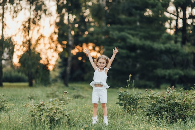 Mała dziewczynka wygląda pięknie w parku o zachodzie słońca