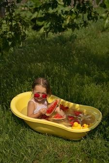 Mała dziewczynka wygląda zza czerwonych okularów przeciwsłonecznych jedząc arbuza w misce z kwiatami