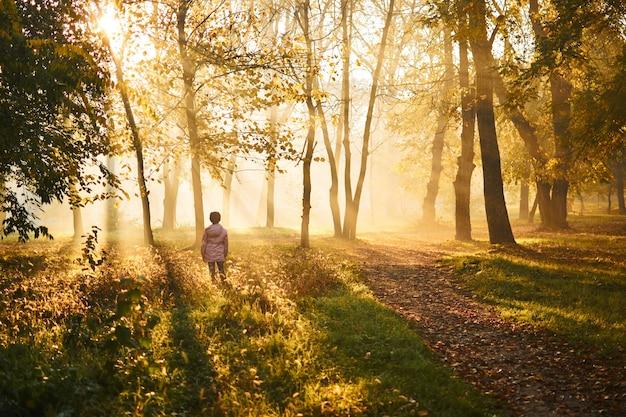 Mała dziewczynka wygrzewa się w słońcu na piękny jesienny mglisty dzień o wschodzie słońca w różowej kurtce