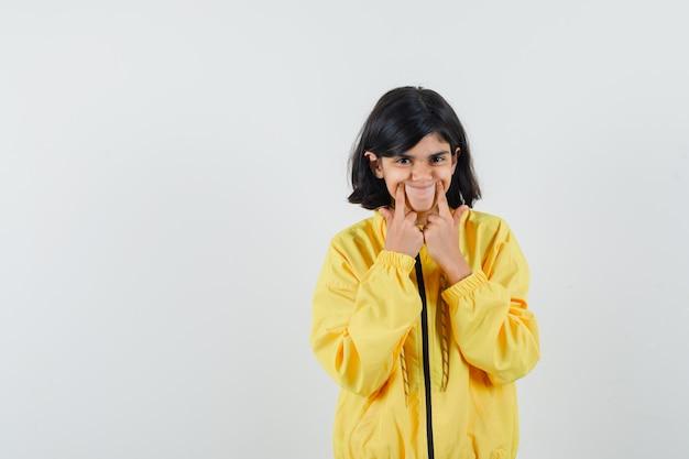 Mała dziewczynka wymusza uśmiech na twarzy w widok z przodu żółta bluza z kapturem.