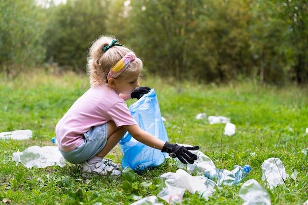 Mała dziewczynka wyrzuca plastikowe śmieci i wkłada je do biodegradowalnego worka na śmieci na zewnątrz. pojęcie ekologii, przetwarzania odpadów i ochrony przyrody. ochrona środowiska.