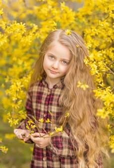 Mała dziewczynka wz żółte kwiaty w dłoniach. dziecko na tle żółtych kwiatów. wiosenny portret dziecka