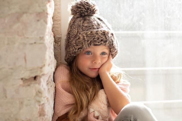 Mała dziewczynka wzorcowa pozuje moda z zima kapeluszem