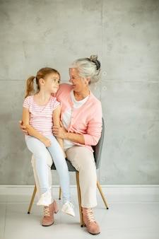 Mała dziewczynka z babcią siedzi na krześle przy szarej ścianie