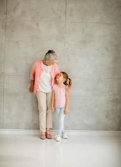 Mała dziewczynka z babcią stojącą przy szarej ścianie