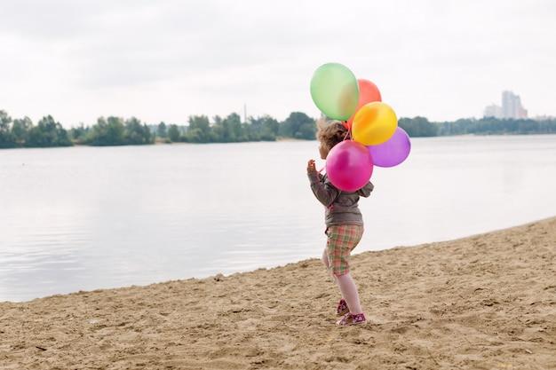 Mała dziewczynka z balonami na piaskowatym brzegu rzeki lub jeziora.