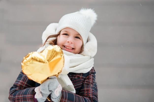 Mała dziewczynka z balonem złote serce. walentynki.