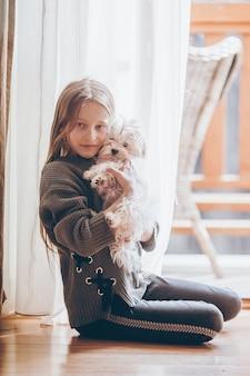 Mała dziewczynka z białym szczeniakiem. szczeniak w rękach dziewczynki