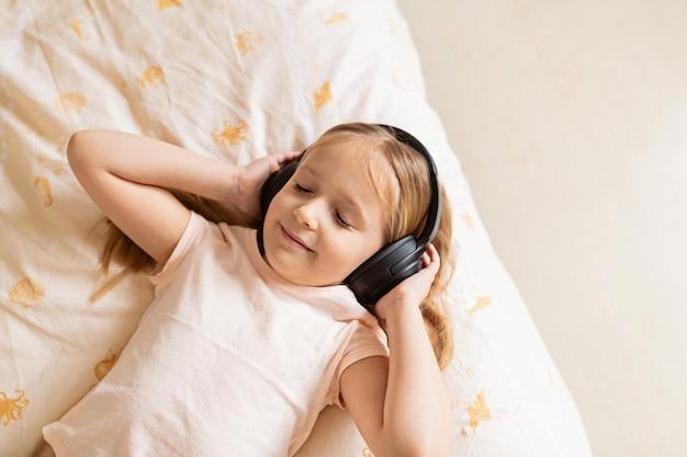 Mała dziewczynka z blond włosami, leżąc na łóżku z bezprzewodowymi słuchawkami