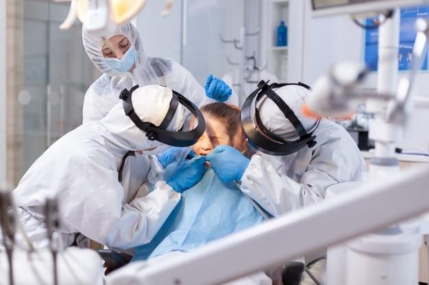 Mała dziewczynka z bólem w trakcie leczenia stomatologicznego, ubrana w kombinezon ochronny i śliniaczek. zespół stomatologiczny ubrany w kombinezon ppe podczas covid19 wykonujący zabieg na zębach dziecka.