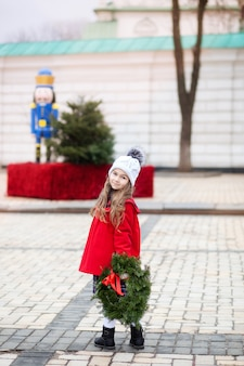 Mała dziewczynka z boże narodzenie wieniec na ulicy