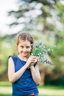 Mała dziewczynka z bukietem polnych kwiatów.