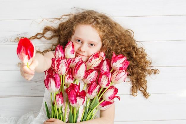 Mała dziewczynka z bukietem tulipany. matka dnia pojęcie, wakacyjny pojęcie.