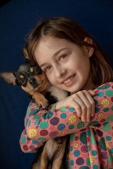 Mała dziewczynka z chihuahua. dziewczyna trzyma chihuahua. dziewczyna ze swoim zwierzakiem w ramionach. chihuahua w kolorze czarno brązowo-białym. dzieci kochają swoje zwierzęta. dziewczyna i chihuahua. dzieci kochają swoje zwierzęta