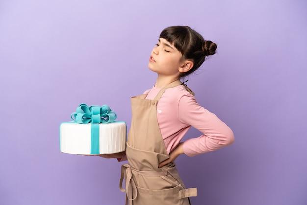 Mała dziewczynka z ciasta trzymająca duży tort na fioletowym tle cierpiąca na bóle pleców za wysiłek