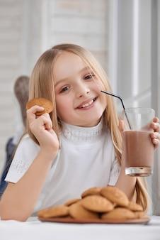 Mała dziewczynka z ciastkami i czekoladowym mlekiem