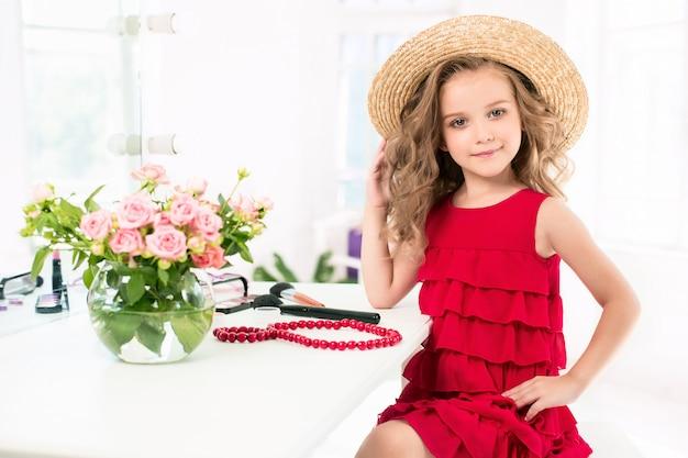 Mała dziewczynka z czerwoną sukienką i kosmetykami.