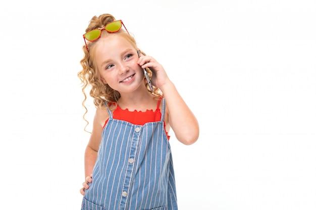 Mała dziewczynka z czerwonymi włosami w czerwonej koszulce i niebiesko-białym prążkowanym kombinezonie rozmawia przez telefon.