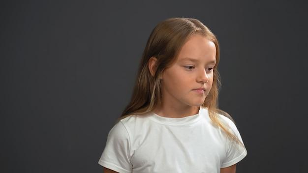 Mała dziewczynka z długimi blond włosami, zamyślona, ubrana w białą koszulkę i czarne spodnie na czarnej ścianie
