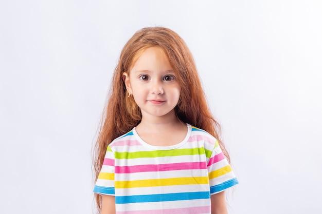 Mała dziewczynka z długimi rudymi włosami uśmiecha się w wielobarwnej koszulce