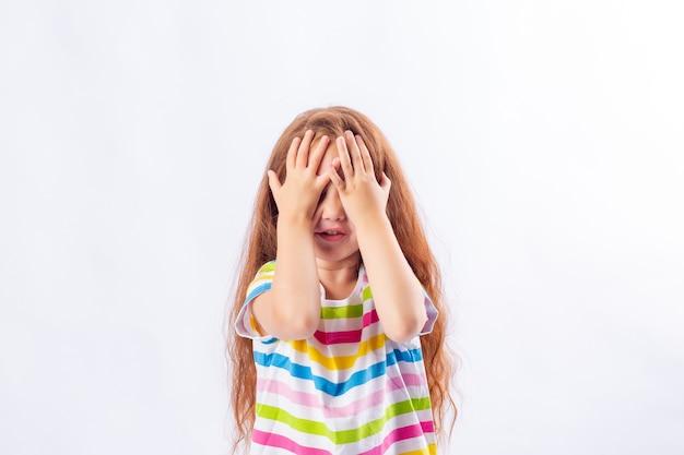 Mała dziewczynka z długimi rudymi włosami w wielobarwnej koszulce ukrywa twarz