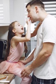 Mała dziewczynka z długimi włosami. ojciec i córka razem. rodzina przygotowuje się do jedzenia.