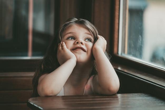 Mała dziewczynka z długimi włosami siedzi przy stoliku w kawiarni. zdjęcie wysokiej jakości