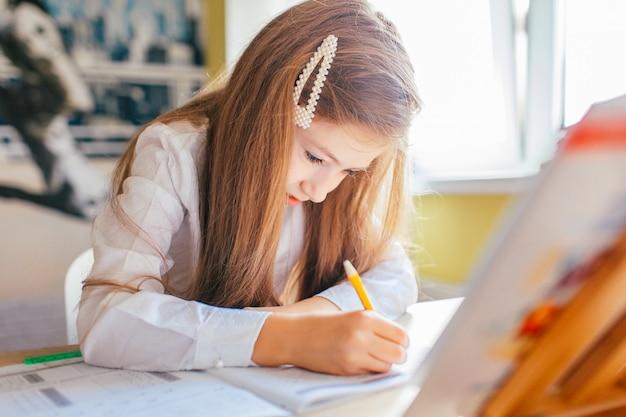Mała dziewczynka z długimi włosami studiuje lub uzupełnia domową pracę na stole z stosem książek i skoroszytu