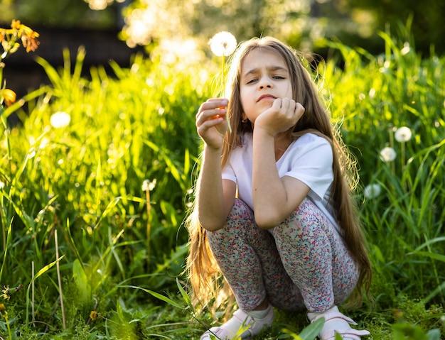 Mała dziewczynka z długimi włosami w koszulce. patrzy podejrzliwie i ze złością, trzymając w rękach puszystego dmuchawca