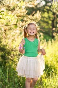 Mała dziewczynka z długimi włosami w sukience o charakterze w lecie