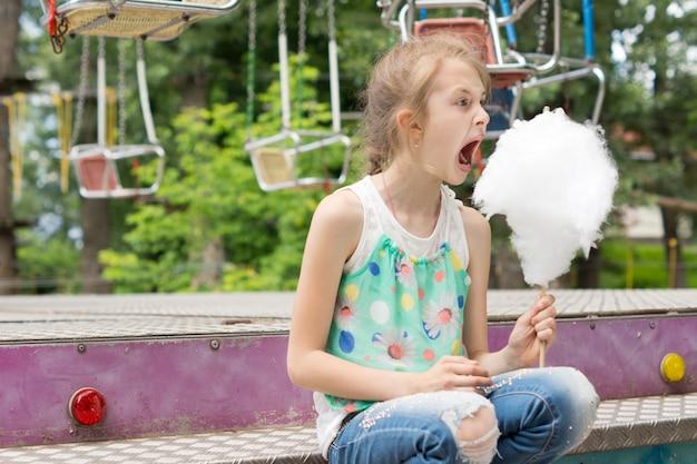 Mała dziewczynka z dużą pałką waty cukrowej