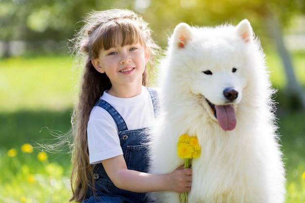 Mała dziewczynka z dużym bielu psem w parku.
