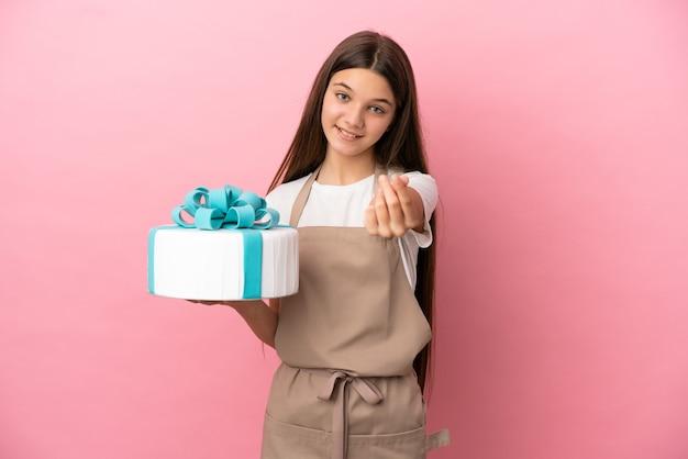Mała dziewczynka z dużym ciastem na odosobnionym różowym tle gestu zarabiania pieniędzy
