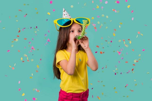 Mała dziewczynka z dużymi okularami przeciwsłonecznymi i konfetti