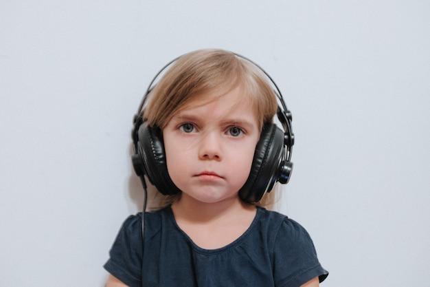 Mała dziewczynka z dużymi słuchawkami w domu