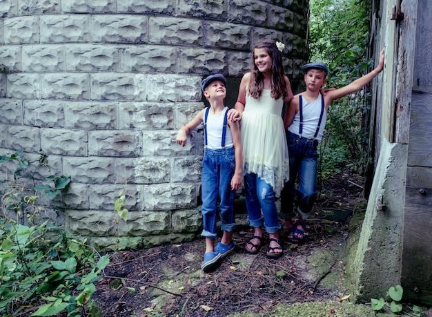 Mała dziewczynka z dwoma braćmi pozuje w pobliżu budynku otoczonego zielenią w słońcu