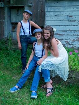 Mała dziewczynka z dwoma braćmi siedzącymi na kamieniu na farmie otoczonej płotami i zielenią