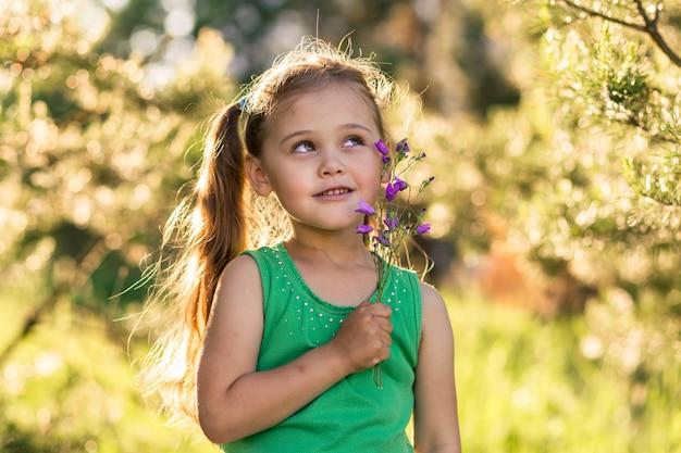 Mała dziewczynka z dzwonkami kwiatów na przyrodę w lecie