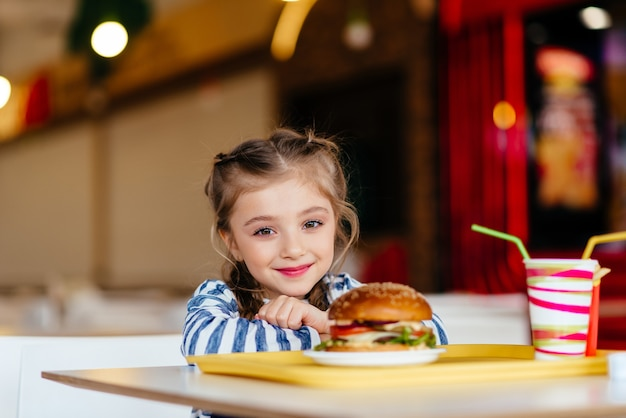 Mała dziewczynka z hamburgerem i napojem gazowanym
