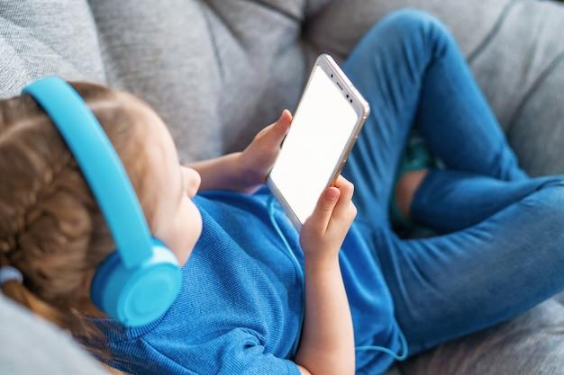 Mała dziewczynka z hełmofonami i mienia smartphone bielu ekranem
