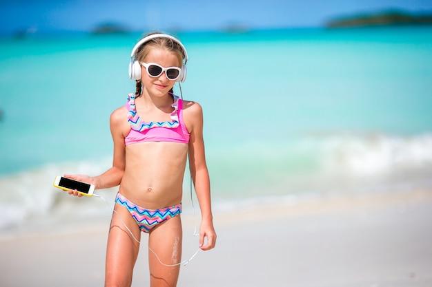 Mała dziewczynka z hełmofonami na plaży
