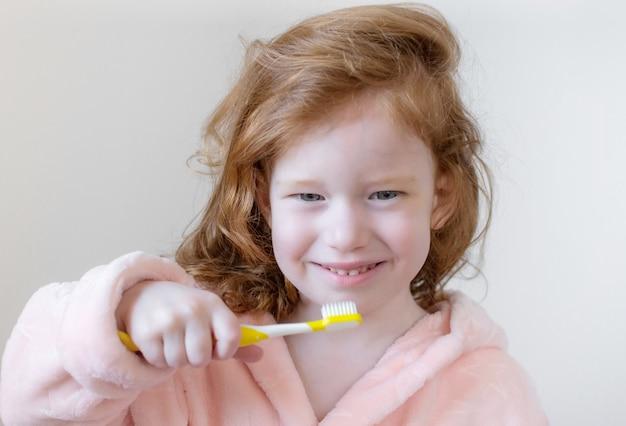 Mała dziewczynka z imbirowymi włosami myjącymi zęby, żółta szczoteczka do zębów, higiena jamy ustnej, poranna noc zdrowy styl życia koncepcja